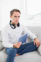 Casual serious young man using digital tablet on sofa