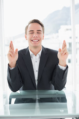 Smiling businessman with fingers crossed at office desk