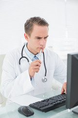 Doctor looking at computer in medical office