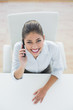Smiling elegant businesswoman using cellphone