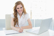 Smiling elegant businesswoman writing document at desk