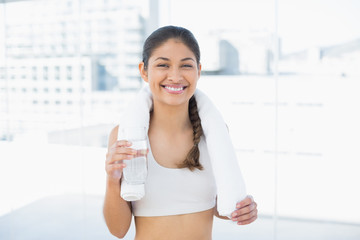 Woman with towel around neck holding water bottle