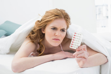 Young woman looking at pills in bed