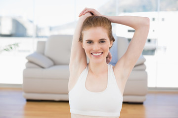 Woman stretching hands behind back in fitness studio