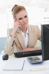 Worried businesswoman with computer at desk