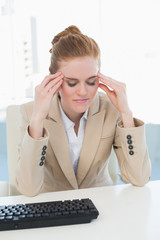 Businesswoman suffering from headache at office