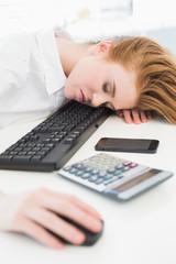 Businesswoman resting head on keyboard