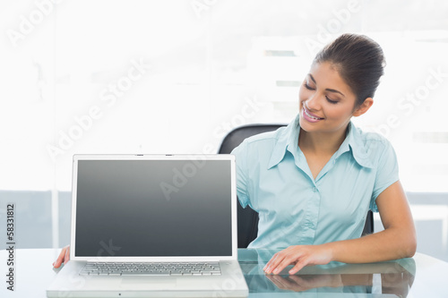 Elegant businesswoman with laptop on desk in office