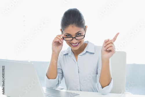 Elegant businesswoman with laptop sitting at desk