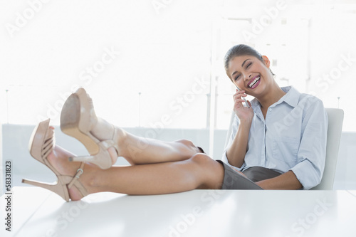 Relaxed businesswoman using cellphone in office