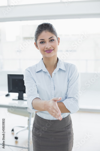 Elegant businesswoman offering a handshake in office