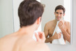 Rear view of man looking at self in bathroom mirror