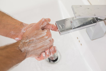 Washing hands with soap under running water