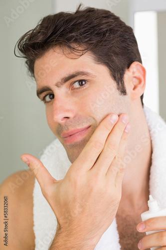 Man applying moisturizer on face