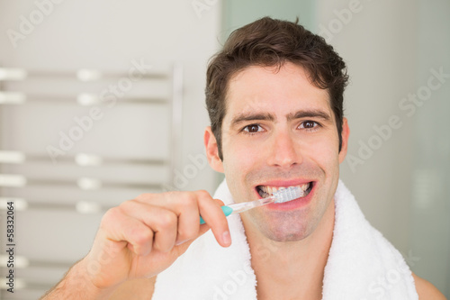 Close up portrait of man brushing teeth in bathroom