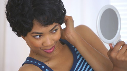 Black woman smiling and winking at mirror while fixing hair