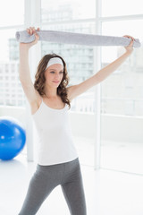 Fit woman holding up towel in a fitness studio