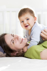 Happy mother and son playing and having fun in bed.