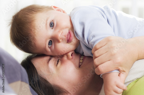 Joyful mother cuddling her baby boy with affection.
