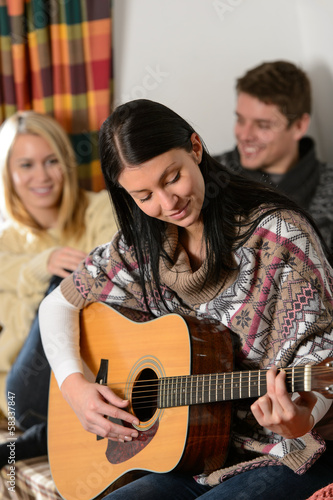 Young friends in winter cottage play guitar
