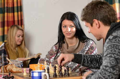 Young couple play chess winter cottage countryside