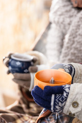 Steaming cups of tea winter hands holding