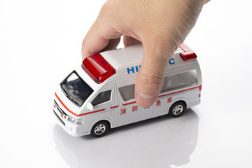 ミニチュアの救急車を持つ手