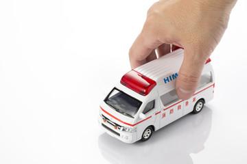 救急車のミニチュアカーを持つ手