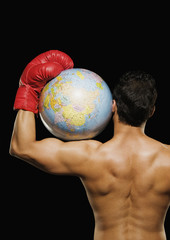 Male boxer holding a globe on his shoulder