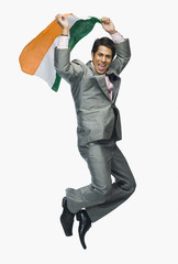Businessman jumping with holding Indian flag