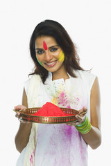 Woman holding Holi colors in a plate