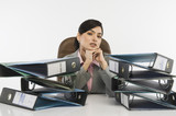 Stack of ring binders in front of a businesswoman