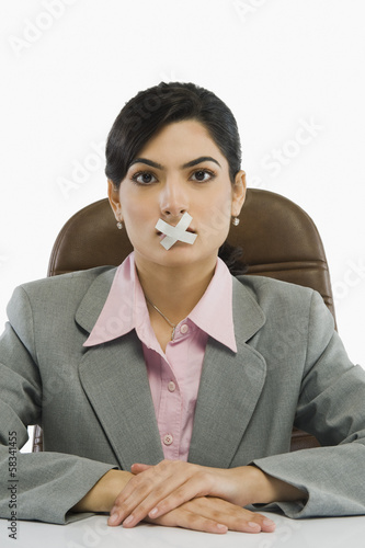 Businesswoman with adhesive tape over her mouth