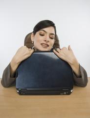 Businesswoman hugging a laptop