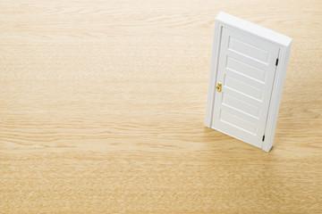 木目の背景にドアの模型