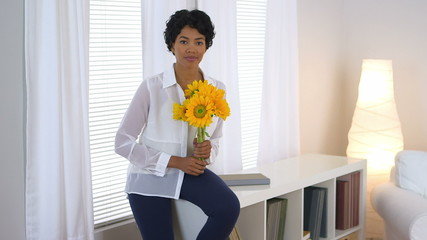 Beautiful African American woman holding sunflowers by window