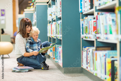 Teacher And Boy Reading Book By Bookshelf