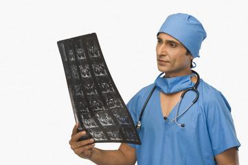 Surgeon examining an x-ray report