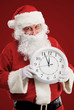 Stunned Santa holding clock showing five minutes to midnight