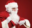 Santa Claus with a bag of presents and looking at his watch
