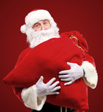 Portrait of Santa Claus embracing huge red sack with gifts