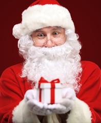Santa Claus giving xmas present and looking at camera