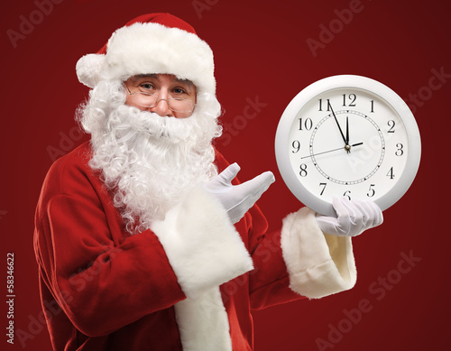 Santa pointing at clock showing five minutes to midnight
