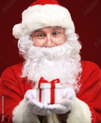 Santa Claus giving xmas present and looking at camera