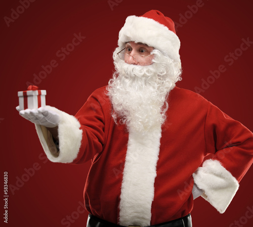 Photo of kind Santa Claus giving xmas present