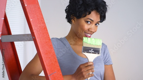 Playful African American woman with paint brush in hand