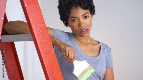 Upset African American woman with paint brush in hand