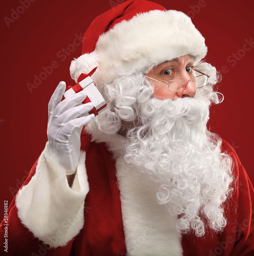 Photo of Santa Claus holding red giftbox by his ear