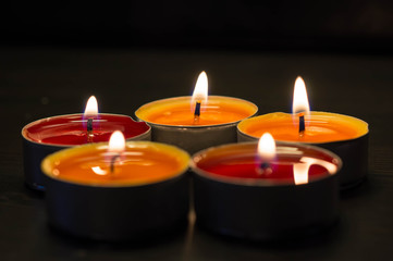 Five burning candles against a dark background