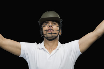 Cricket batsman celebrating with his arms raised